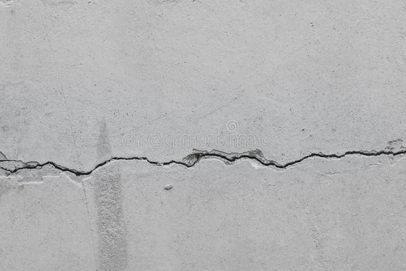 Crack in an old concrete wall. Old concrete wall with crack texture background cracked concrete wall covered with grey cement royalty free stock photos