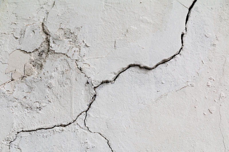 Crack. Texture of old painted white plaster. Cracked wall. royalty free stock photo