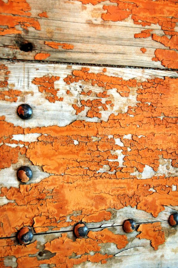 Cracked and Aging Orange Paint. Detail of old wooden door with peeling orange paint and iron bolts stock image