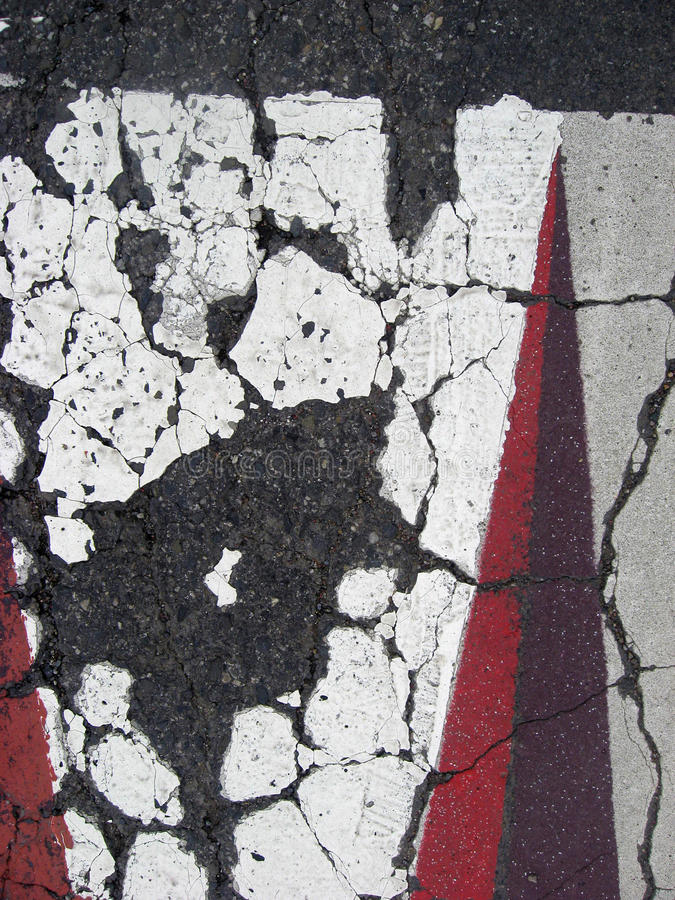 Cracked asphalt texture. Cracked paint on asphalt and concrete stock photography