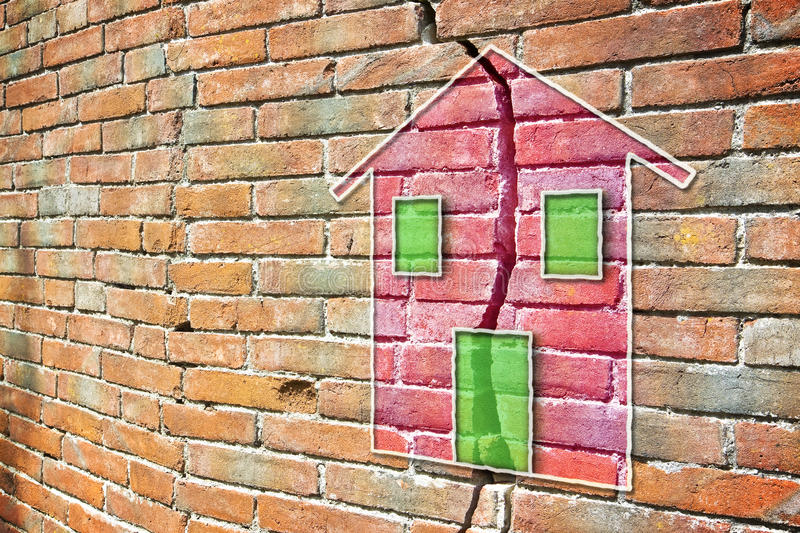 Cracked brick wall with a colored house drawn on it stock photography
