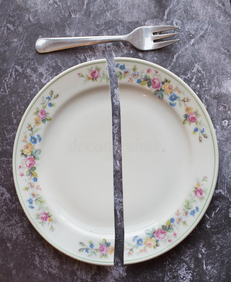 Broken dish with a fork on grey surface stock image