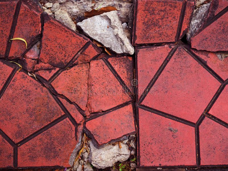 Cracked red clay geometric tile floor background. Cracked broken dirty black stained red clay random geometric shape tile footpath floor, grainy texture concrete stock photography