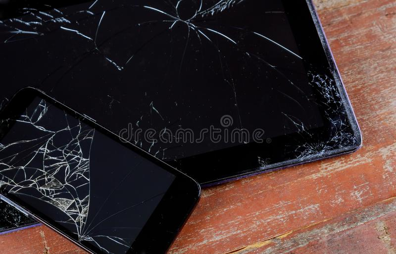 Cracked broken phone and tablet screen closeup. Cracked broken phone black touch screen tablet with broken closeup accident smartphone scratch technology glass royalty free stock images