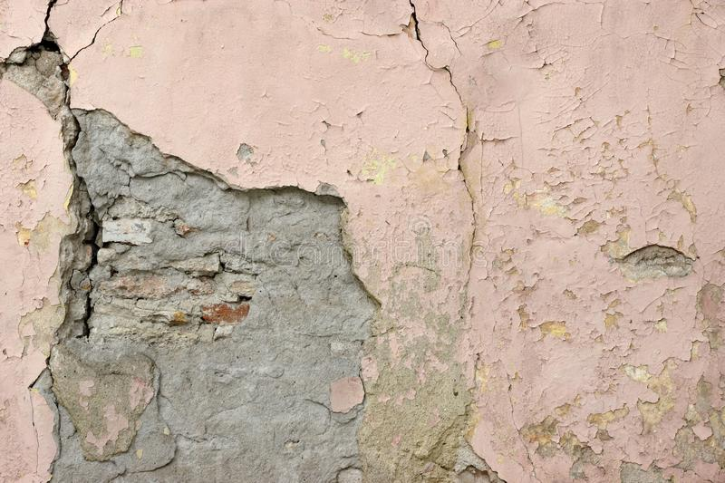 Cracked Building Stone Wall With Fractured Plaster Covering Tex. Cracked Building Stone Wall With Fractured Plaster Covering And Weathered Paint Texture royalty free stock photography