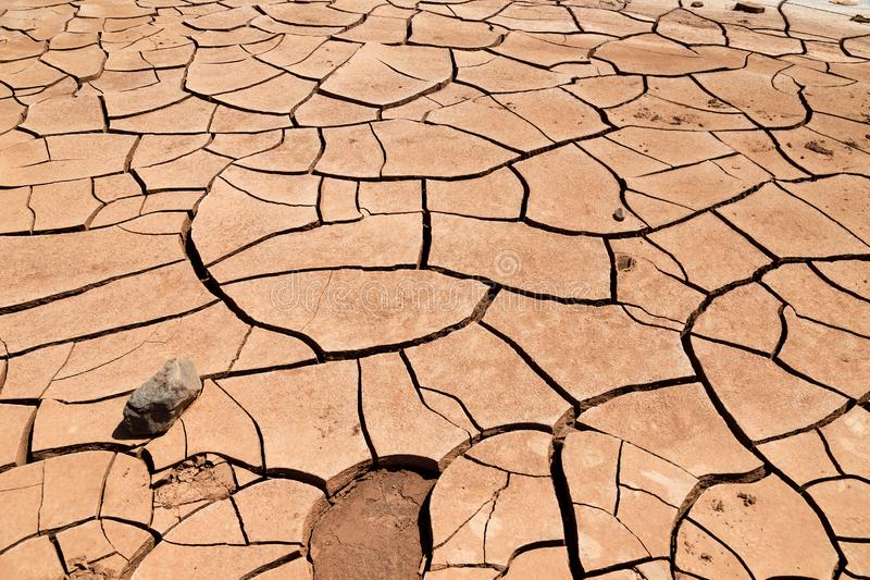 Cracked clay soil in front of the Flaming Mountains in China, Xinjiang province. Located in the Turpan depression. This site in summer is extremely dry and hot stock photography