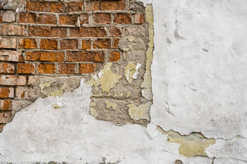 Cracked concrete vintage brick wall. Cracked putty on the wall and brick that looks through the cracked surface of the stock photos