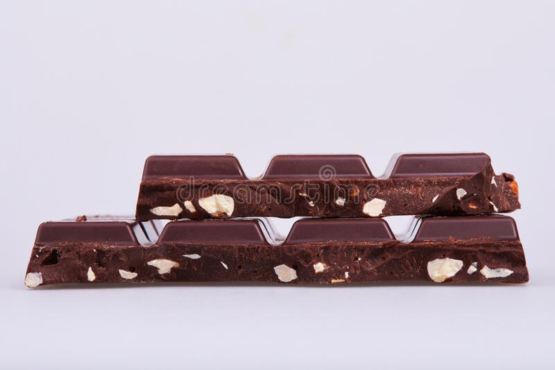 Cracked dark chocolate bars with hazelnuts on white background. Close-up of chocolate pieces royalty free stock photos