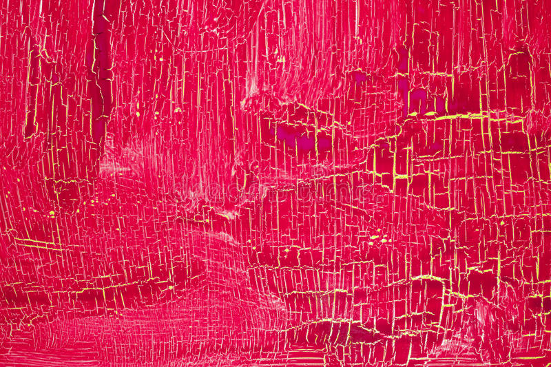Cracked dark red pink paint on the yellow surface stock images