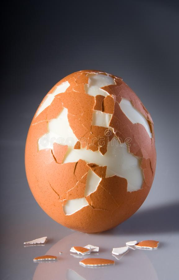 Cracked egg with pieces of shell stock photos