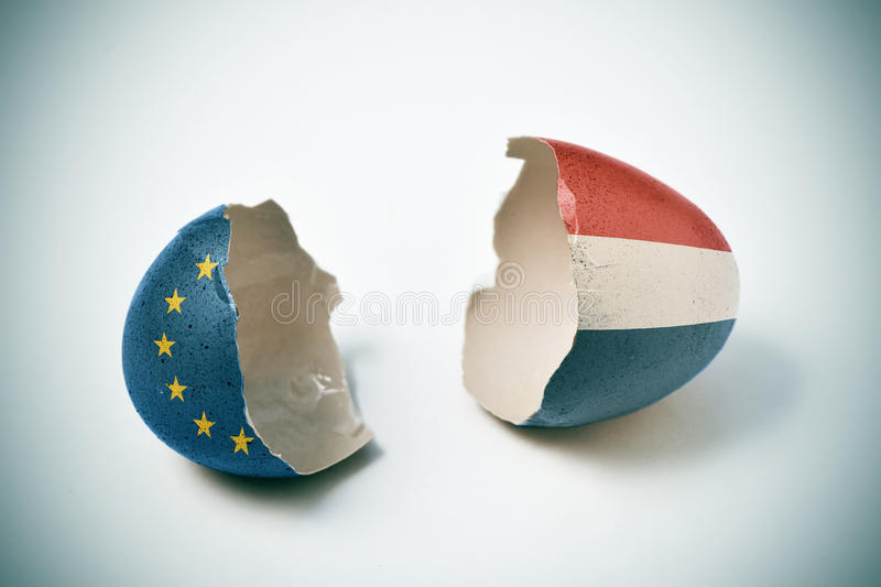Cracked eggshell patterned with the European and the Dutch flag stock photo