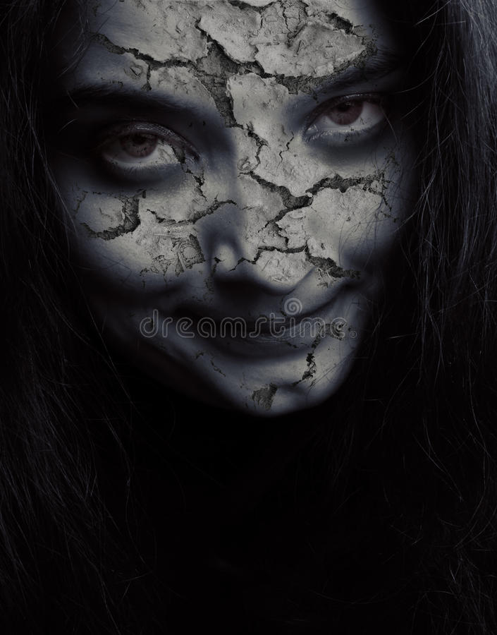 Cracked evil face. Close up on angry evil upset scary woman royalty free stock image