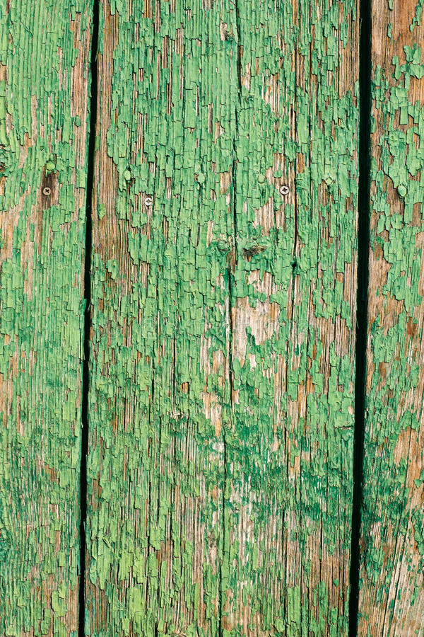 Cracked green paint background. Old cracked green paint on wooden surface textured background vertical frame stock photos