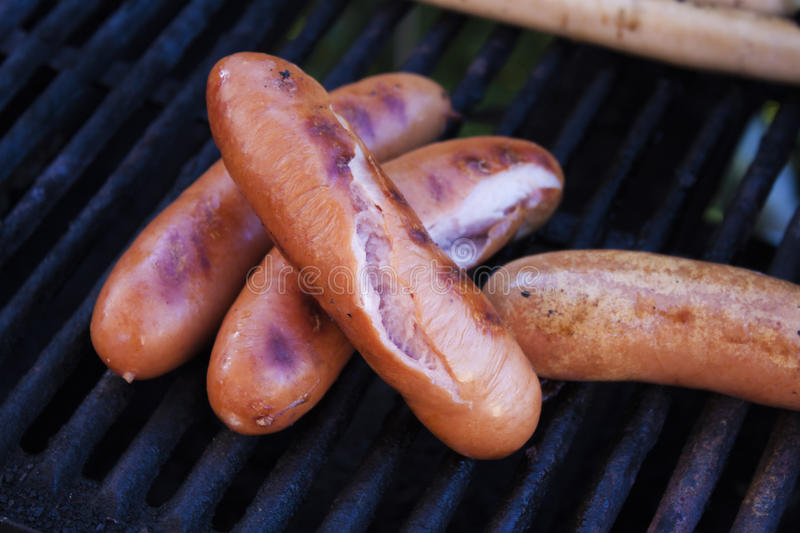 Cracked grilled sausages. On a barbeque royalty free stock image