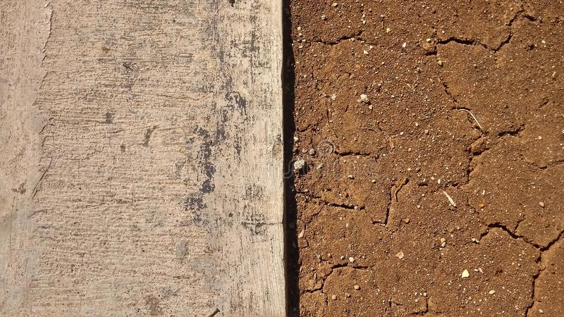 Cracked ground brown and cement cut in the middle for the background royalty free stock photo