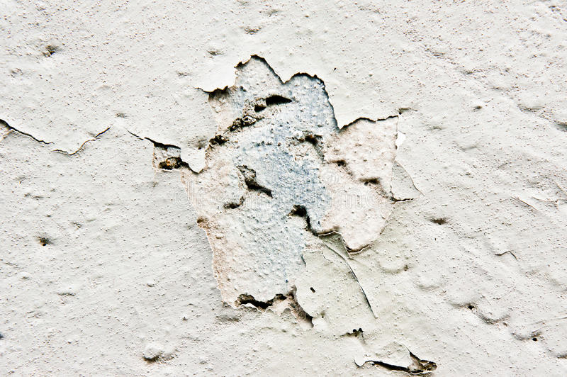 Cracked paint. A defect in a painted wall with exposed stone royalty free stock photo