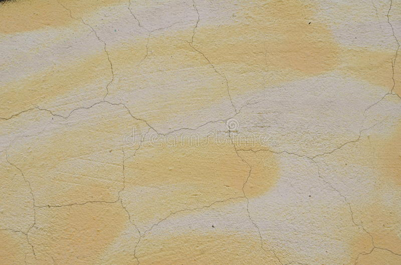 Cracked painted plaster. Cracked plaster airbrushed with beige and white graffiti paint royalty free stock photos