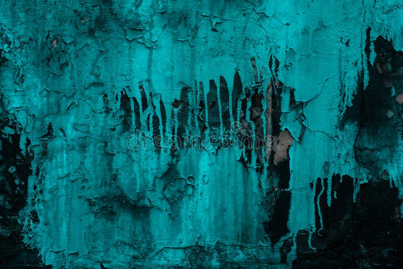 Cracked painted wall black in abstract style on turquoise paint background. Rough textured rock. Abstract architecture. Space grun stock photo