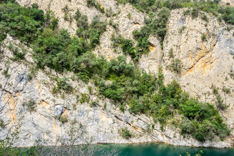 Cracked rock with green plants and trees in a natural park congost de Mont-rebei Monrebey in Spain with blue river, gorge and. Cracked mountain rock with stock photo