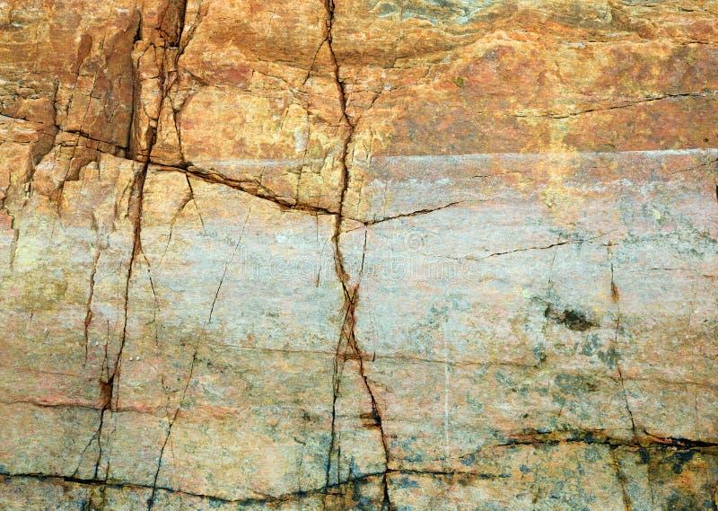 Cracked rock on seacoast backdrop. The cracked yellow rock on seacoast backdrop stock images