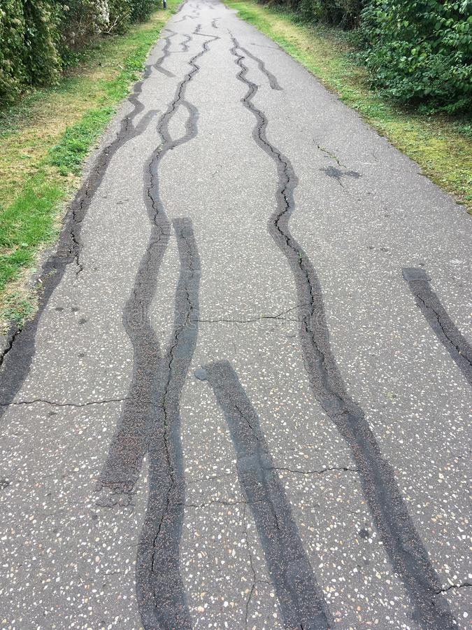 Cracked Tarmac Footpath royalty free stock image