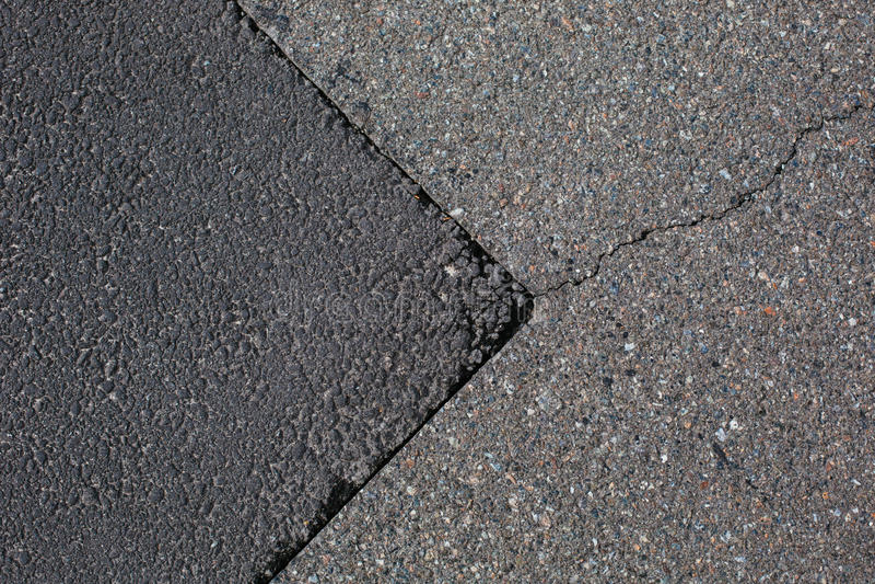 Cracked tarmac road surface. Grey cracked tarmac road surface royalty free stock photography