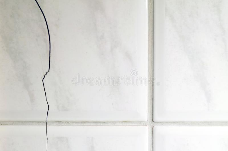 Cracked tiles on the bathroom wall stock images
