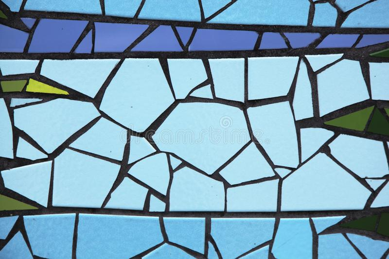 Cracked tiles in different colors arranged on a wall. Cracked tiles in various colors arranged neatly on a wall forming a piece of art stock images