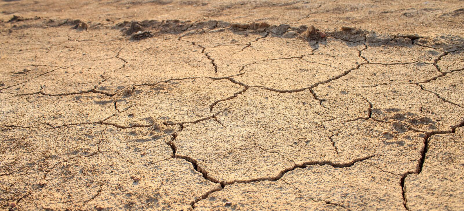 Cracked waterless ground. Natural disasters. Cracked waterless ground at summer drought . Natural disasters desert background stock photo