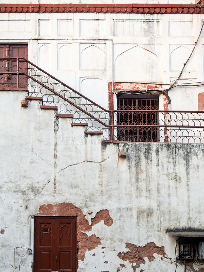 Cracked Weathered Building with Rusty Doors India. An old building with white cracked plaster and rusty doors and railings in Delhi, India royalty free stock photo