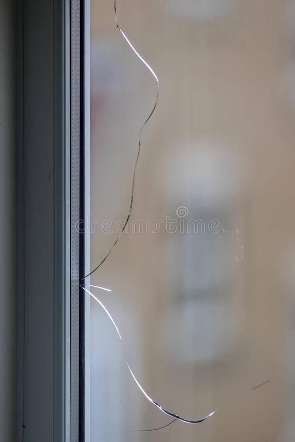 Cracked window. Broken glass pane in double-glazing. Cracked window pane in a modern double glazed UPVC window. Broken glass crack in damaged double-glazing royalty free stock images