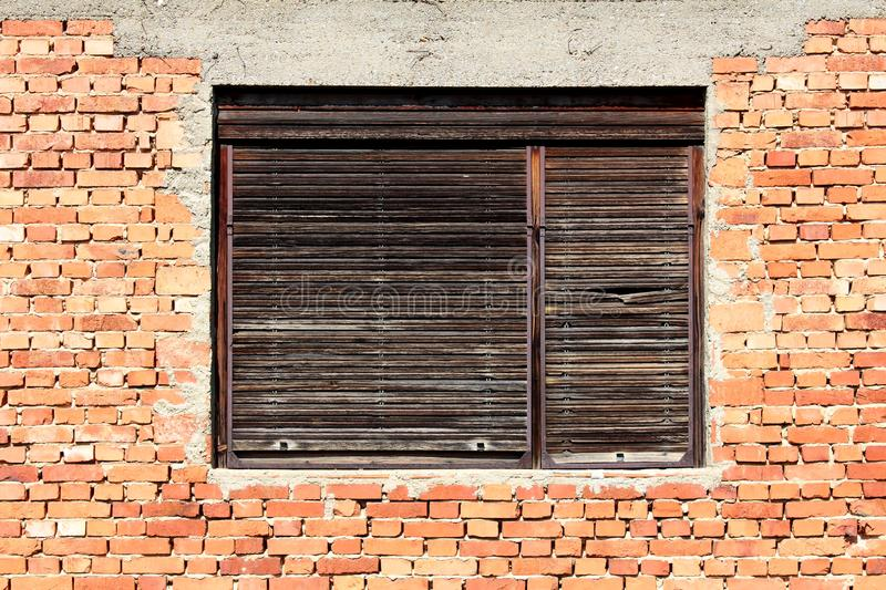 Cracked wooden window blinds on old dilapidated window frame mounted on red brick and concrete wall of abandoned family house royalty free stock image