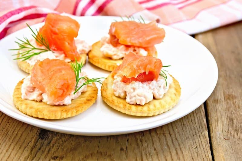Cracker con crema ed il salmone a bordo immagini stock libere da diritti