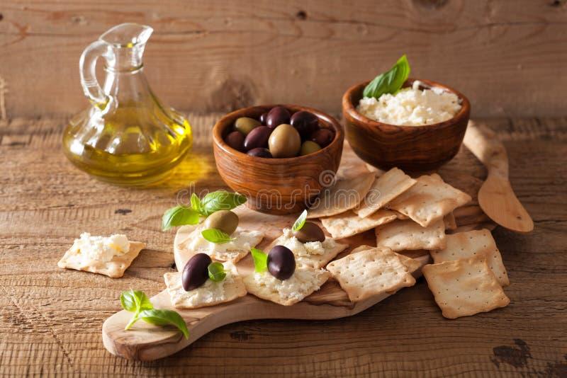Cracker con formaggio a pasta molle ed olive Aperitivo sano fotografia stock libera da diritti