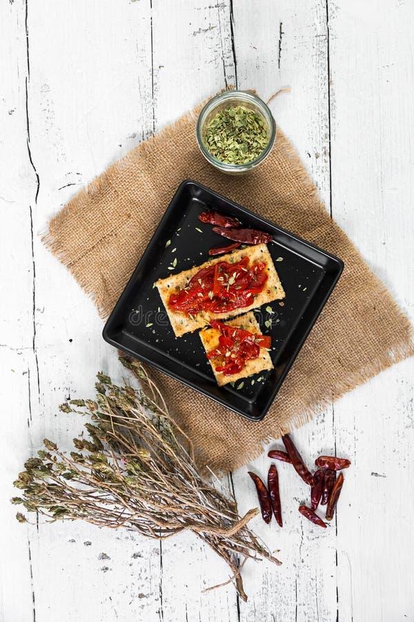 Cracker con i peperoni, il peperoncino e l'origano arrostiti immagini stock