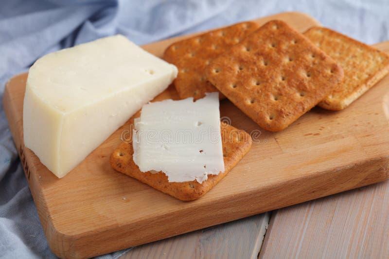 Cracker con il formaggio del latte di capra del gouda sul bordo di legno fotografie stock