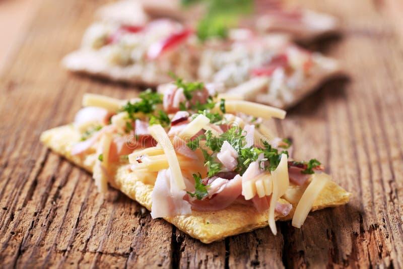 Cracker con la guarnizione del formaggio e della pancetta affumicata fotografia stock
