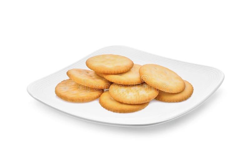 Cracker del biscotto nel piatto bianco isolato su bianco immagini stock