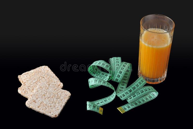 Cracker del riso, un vetro di succo d'arancia e nastro di misurazione fotografia stock