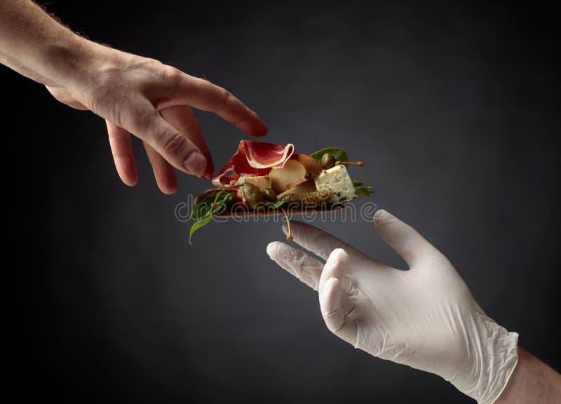 Cracker della segale con formaggio blu, il prosciutto di Parma e la pera guarniti con i capperi e il cornichon immagine stock