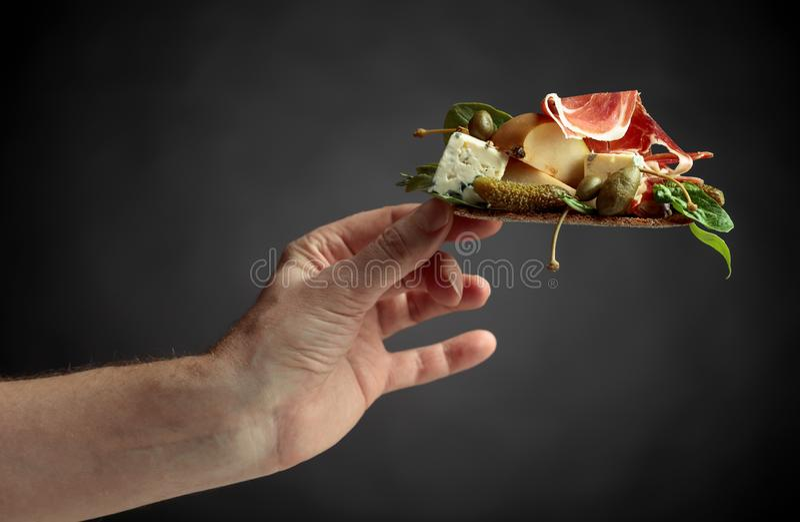 Cracker della segale con formaggio blu, il prosciutto di Parma e la pera guarniti con i capperi e il cornichon fotografie stock