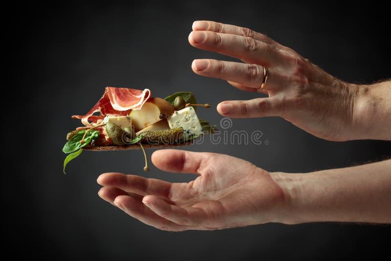 Cracker della segale con formaggio blu, il prosciutto di Parma e la pera guarniti con i capperi e il cornichon immagini stock