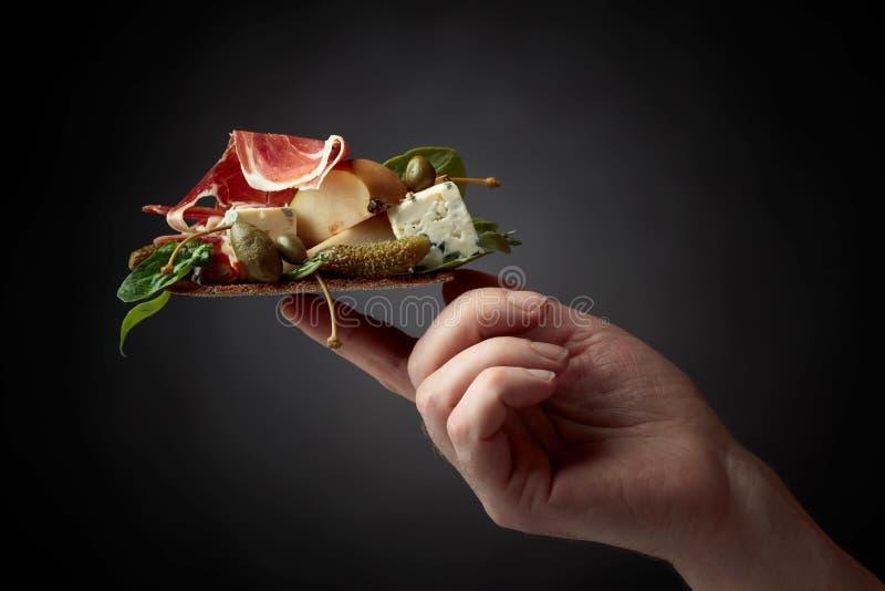 Cracker della segale con formaggio blu, il prosciutto di Parma e la pera guarniti con i capperi e il cornichon fotografia stock
