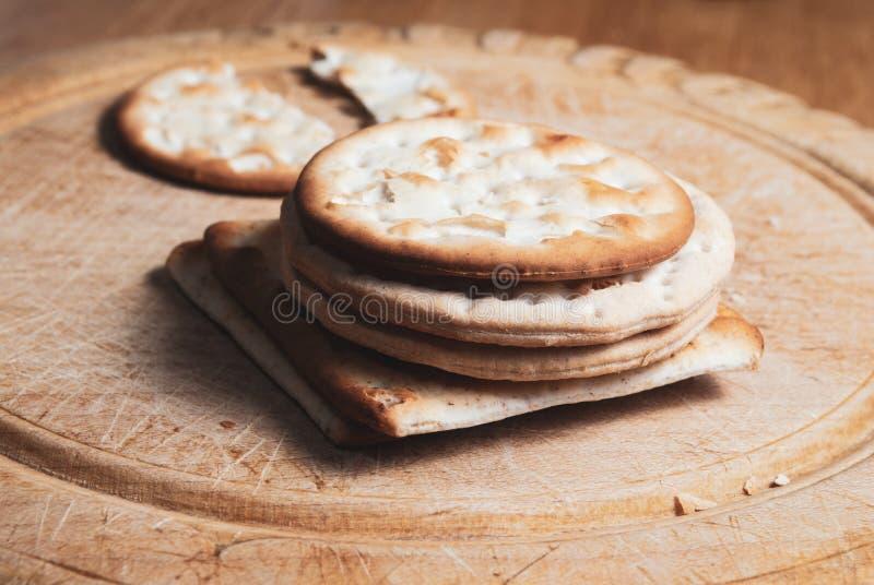 Cracker gestapelt auf Weinlese-Brot-Brett lizenzfreies stockbild