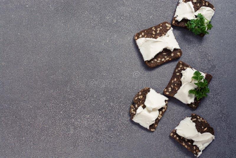 Cracker mit Gewürzen und Käse auf einem grauen Hintergrund Italienische Roggencracker Ansicht von oben lizenzfreies stockfoto