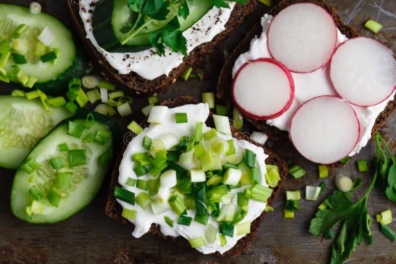 Cracker mit Hüttenkäse, Rettich, der Gurke verziert mit Kressesalat und den frischen Kräutern stockfotos