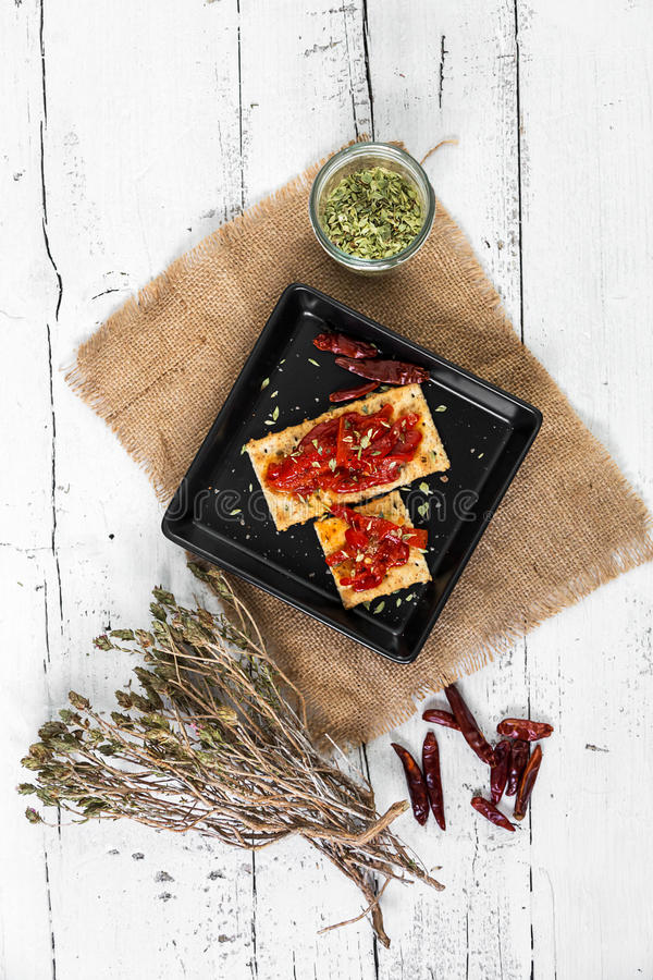 Cracker with roasted peppers, chili pepper and oregano stock images