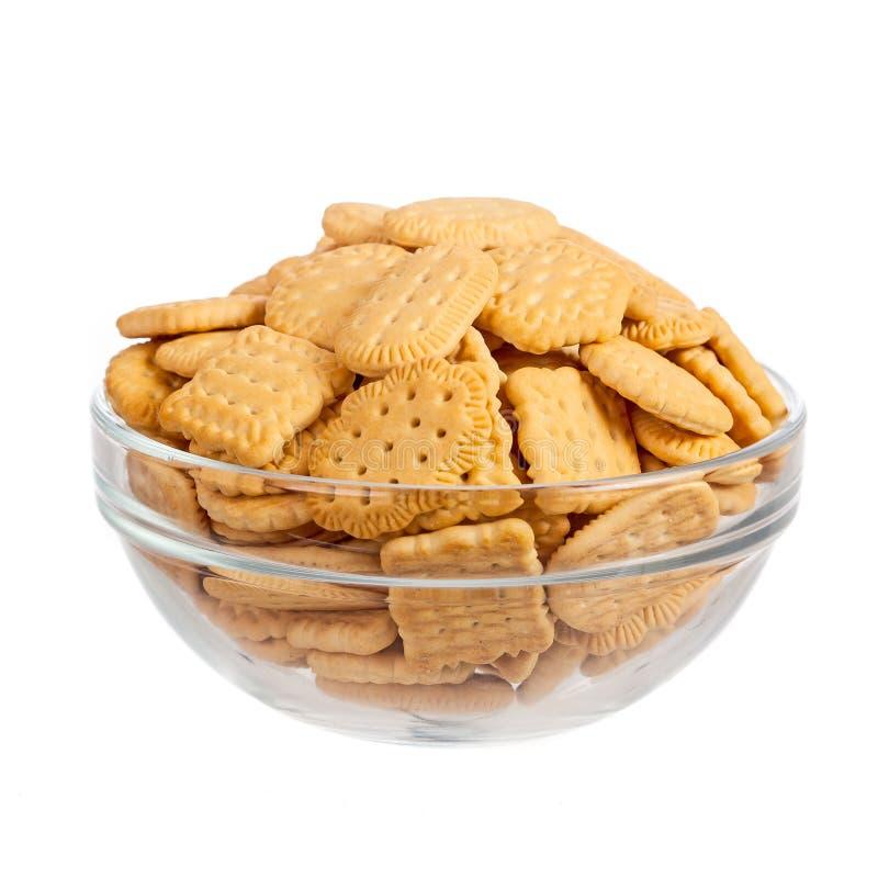 Crackers in glaskom die over wit wordt geïsoleerd stock afbeelding