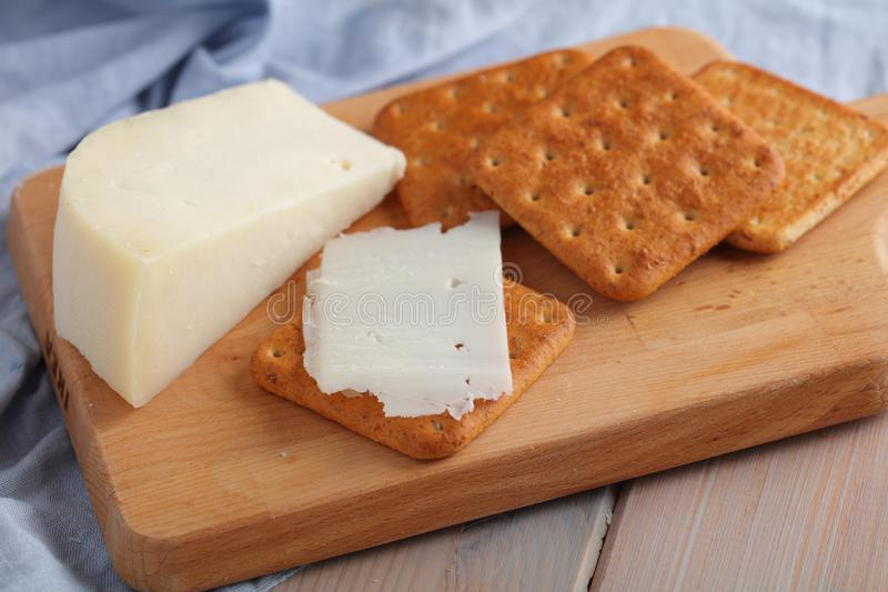 Crackers with Gouda Goat Milk Cheese on wooden board stock photos