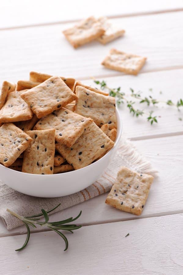Crackers met kruiden en zwarte sesamzaden op lijst stock foto